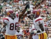 USC's Dwayne Jarrett (8) celebrates his touchdown with teammate Dominique Byrd. The Trojans beat Hawaii, 63-17, Saturday in Honolulu.