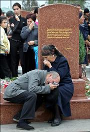 Grandparents, no names given, of Boris Dzhibilov, 9, who was killed in the school hostage taking, cry at their grandson's gravestone Saturday at the cemetery in Beslan, Russia. Thousands of residents of the small town of Beslan on Saturday marked the first anniversary of one of Russia's deadliest terrorist attacks.