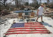Retired Army Gen. Randolph Bourgeuis walks around an American flag he recovered Monday from his home which was destroyed by Hurricane Katrina in Bay St Louis, Miss.