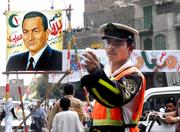 An Egyptian traffic soldier gestures in front of a poster promoting President Hosni Mubarak, leader of the ruling National Democratic party, in Cairo, Egypt, Tuesday, a day before 10 candidates run in the country's first ever multi-candidate presidential elections, including veteran President Hosni Mubarak.