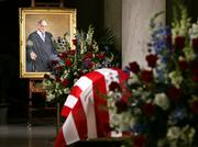 The coffin bearing the body of Chief Justice William H. Rehnquist lies in the Great Hall of the U.S. Supreme Court, under the view of his official portrait painted in 1994 by artist Thomas Loepp.