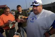Kansas University football coach Mark Mangino, right, speaks with reporters after practice. Mangino announced Wednesday that freshman quarterback Kerry Meier would return to practice Monday after he successfully underwent a procedure to fix a heart ailment that was detected in preseason screening.