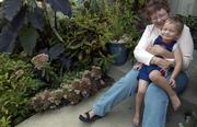 Clayton Goodell, 3, smiles as he fidgets in his grandma Karen Goodell's lap in her front yard. Goodell's garden serves as a good example of using a well-planned combination of plants and flowers to create the layered, mature look found in garden magazines.