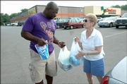 Volunteer Kevin Johnson, Lawrence, left, accepts supplies from Gloria Morton, Lawrence, as she makes her second donation of the day to Waves of Relief, an all-volunteer disaster relief organization, which is collecting essential items and money for Hurricane Katrina survivors through this weekend in the Checkers parking lot, 23rd and Louisiana streets.