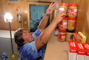 Jo Lee, Eudora, the food coordinator at Penn House, organizes the few items in the agency's food pantry.