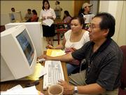 Haskell Indian Nations University registrar Manny King, right, works with sophomore Leah Elliott, Pawhuska, Okla., to format her schedule of classes for the approaching semester during enrollment Aug. 22 at Navarre Hall. Event dates have been announced for the 2005-2006 calendar.