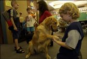 Schwegler School first-grader Brandon Taylor, 6, introduces himself to his new classmate, a training dog named Gemini, as his new teacher Lisa Clark speaks with two of her former students, James and Jasmine Harader-Ellett, Aug. 16 during new student orientation at the school.