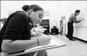 Jamie Fischer, an eighth-grader at Bishop Seabury Academy, takes notes during an algebra class taught by Orlando Ventura, right. The private school touts its academic curriculum, including Latin language study for seventh- and eighth-graders.