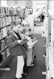 From left, Olivia Fox, 11, and her sister Emalee, 7, look at books while their mother, Laura Fox, Lawrence, searches the shelves at the Lawrence Public Library in this March file photo. The Lawrence City Commission would like to expand the 45,000-square-foot library.