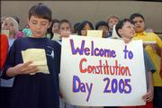 Hillcrest sixth-graders Andrew Carttar, 11, left, and Issac Rinke, 11, celebrate Constitution Day by reading the preamble to the U.S. Constitution on Friday afternoon in front of Wescoe Hall at Kansas University. Across campus, more than 140 people became U.S. citizens at the Dole Institute of Politics. Schools around the country study the Constitution.