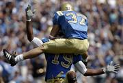 UCLA's Andrew Baumgartner (37) celebrates his touchdown catch against Oklahoma with teammate Marcedes Lewis. The Bruins beat the Sooners, 41-24, Saturday in Pasadena, Calif.