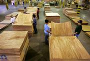 Workers carry plywood at a factory in Curitiba, Brazil. Amid soaring prices for building materials in the United States caused by Hurricane Katrina, Brazil's wood industry is poised to ramp up production, betting plywood exports to the U.S. could increase $500 million this year alone.