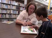 "Heidi Randal, of Lawrence, helps her son, Dominic Randal, with a word as they read the book ""Too Big, Too Small, Just Right"" in the children&squot;s room at the Lawrence Public Library."