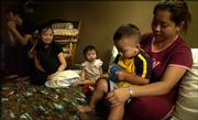 Ngan Hoang sits with her son, Hung Hoang, 2, alongside Dong Tran, left, wife Hong Bui and daughter Trish Nguyen, 1, Friday as the families settle into a temporary home in East Lawrence after being displaced from their homes in Biloxi, Miss., after Hurricane Katrina.