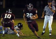 Lawrence High running back Nolan Kellerman utilizes a block by Kyle Mendenhall (10) on Shawnee Mission East&#39;s Bryant Condie in the first half of the Lions&#39; 44-17 victory. Mendenhall later suffered a broken leg in the victory Friday at Haskell Stadium and won&#39;t play again this season.