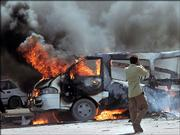 An Iraqi man covers his face approaching a burning minibus at the scene of a suicide bombing Friday in Baghdad, Iraq. A suicide bomber riding on a small public bus set off hidden explosives in a bustling open-air bus terminal Friday, the Muslim day of worship, killing at least five people and wounding eight, police said.
