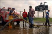 Members of the Fairview Township Fire Department work to drain water from the Perry-Lecompton High School football field. Despite the removal of 270,000 gallons of water, the heavy rains caused Friday night's home game to be moved to the opposing team's field at Santa Fe Trail High School in Carbondale.