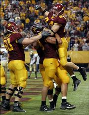 Minnesota wide receiver Logan Payne, top right, and teammates Mike Nicholson, left, and Matt Spaeth savor a touchdown in the first overtime. The Gophers beat No. 11 Purdue, 42-35 in double overtime, Saturday in Minneapolis.