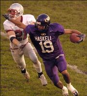 Haskell Indian Nations University wide receiver Hunter Smith (19) stiff-arms Friends University defensive back Dan Kontz during the first half. The Fightin' Indians lost, 29-10, Saturday night at Haskell Stadium.