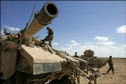 "Israeli soldiers move tanks into position at a staging area just outside the northern Gaza Strip. Israel ordered ground forces to the Gaza border Saturday and threatened a ""crushing"" response after Israeli towns were hit by the first major Hamas rocket barrage from the coastal territory since Israel&squot;s pullout two weeks earlier."