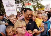 Anti-war activist Cindy Sheehan, second from right, shares a moment with the Rev. Jesse Jackson, center, during an anti-war protest march in Washington. At right is singer Joan Baez. Tens of thousands of marchers on Saturday protested the war in Iraq.