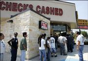 A line forms around the outside of a check-cashing business Thursday in Houston as people prepared for the arrival of Hurricane Rita. Many of the people in line were unable to get checks cashed as the business ran out of cash. Experts say ready access to financing is important during any disaster, whether it's a hurricane, flooding or job loss.