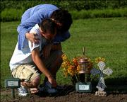 Patti Wood comforts her son K.P. as they visit the grave of their dog Katie at a pet cemetery near Solomon. They wanted their beloved dog, a 70-pound English setter-blue heeler mix, to be buried in a special place and chose the Faithful Friends Memorial Garden.