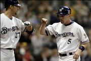 Milwaukee Brewers' Geoff Jenkins, right, is congratulated by Brady Clark, left, after scoring against the Cincinnati Reds. Milwaukee beat Cincinnati, 12-9, Monday in Milwaukee.