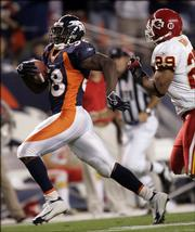 Denver running back Mike Anderson, left, outraces Kansas City safety Sammy Knight to the end zone for a 44-yard touchdown run in the first quarter. The Broncos won, 30-10, Monday in Denver.