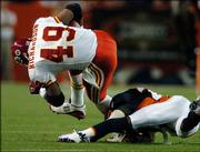 Kansas City's Tony Richardson (49) gets tripped up by Denver cornerback Champ Bailey in the second quarter of the Broncos' 30-10 victory. Denver routed K.C. on Monday in Denver.