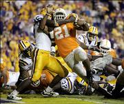 Tennessee running back Gerald Riggs Jr. (21) drives into LSU linebacker Cameron Vaughn en route to scoring the winning touchdown in overtime of the Volunteers' 30-27 victory. The 10th-ranked Vols beat the fourth-ranked Tigers on Monday in Baton Rouge, La.