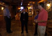 Brad Burke, assistant attorney general with Alcoholic Beverage Control, center, listens to Tom Devlin, right, co-owner of The Hawk, 1340 Ohio, as Burke, Tom Groneman, left, and Kay Ediger, also with ABC, make a walk-through inspection of the Lawrence bar Wednesday afternoon. The ABC is seeking to revoke the liquor license of The Hawk because of repeated underage-drinking citations.