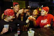 Chi Omega sorority sisters from left, Sam Rasmussen, a Sioux Falls, S.D., senior, Lindsey Jones, a Prairie Village senior, Laura Wolowicz, a Frisco, Texas, senior, and Jacquelyn Roemeling, a Wichita senior, take shots at The Hawk on Wednesday after delivering invitations to an upcoming pirate-theme party. The Kansas Alcoholic Beverage Control wants to revoke the bar's liquor license after citing the bar 18 times in the past three years for serving alcohol to minors.