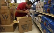 A.R. Wells, store manager for Westlake Ace Hardware, 601 Kasold Drive, unpacks Christmas lights Thursday at the store.