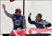 NASCAR veterans Rusty Wallace, left, and Mark Martin wave to the crowd as they are driven around the Dover Speedway. Wallace and Martin were acknowledged before the start of Sunday's MBNA 400 in Dover, Del.