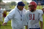 Oskaloosa High football coach Brad Reed talks with Mitch Lowe during Wednesday's practice. Reed is also the school's principal.