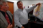 Oskaloosa High principal Brad Reed, right, discusses possible changes to the school's sports district Wednesday with . Loren Lutes, Oskaloosa's superintendent of schools.