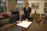 In this photo provided by the White House, President Bush signs the commission appointing John Roberts, right, as the 17th chief justice of the United States before swearing-in ceremonies.