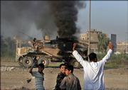 An Iraqi man raises his hands looking at a burning US military vehicle Thursday in Baghdad, Iraq.