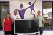 Chris Randolph, right, receives his new television donated by Rent To Own Center on Sept. 7. Randolph was the grand prize winner for the 2005 Bowl For Kids' Sake event, which raises money to support Big Brothers Big Sisters of Douglas County. Randolph is pictured with Becky Price, regional executive director of Kansas Big Brothers Big Sisters, and Hank Booth, 2006 Bowl For Kids' Sake co-chair.