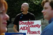 Douglas County resident Rolland Hagedorn shows his support for the Douglas County AIDS Project Friday at a rally at Kansas University.