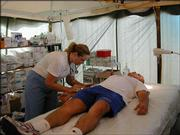 Emergency room Nurse Karin Feltman treats a patient while volunteering in Mississippi after Hurricane Katrina.
