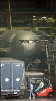 Boeing Co. workers unload parts from a truck Friday at the company's aircraft assembly plant in Everett, Wash., one day after striking Machinist Union workers voted to approve a new labor contract. The agreement ended a four-week strike that shut down Boeing's commercial airplane assembly plants.