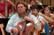 Cellist Jesse Henkensiefken, 24, of Topeka, waits for his cue during a Kansas University Symphony Orchestra rehearsal. The group opens its season with a concert at 7:30 p.m. Friday at the Lied Center.