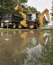 A backhoe dumps flood damaged property from the Dannefer home Monday in Rossville. Flash flooding caused parts of the town to be evacuated. A 1994 proposed flooding-control project was defeated by 12 votes, a plan which some say could have limited the recent flooding.