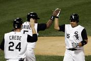 Tadahito Iguchi, right, accepts congratulations from teammates Joe Crede (24) and Juan Uribe (5) after hitting a three-run fifth-inning homer. The White Sox defeated the Red Sox, 5-4, Wednesday in Chicago to take a 2-0 series lead.