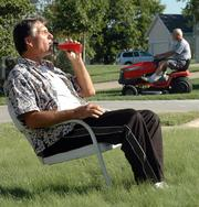 Lawrence resident Jeff Morrow enjoys a beverage on his property in the 4600 block of Trail Road while his neighbor mows. Morrow says his buffalo grass lawn requires very little maintenance.