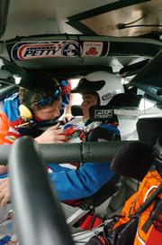 Journal-World sports editor Tom Keegan squeezed into a Richard Petty Driving Experience car for a ride with Busch Series driver Johnny Sauter. Keegan and Sauter reached 170 mph during the ride Wednesday at the Kansas Speedway. The NASCAR Busch and Nextel series races are this weekend at the speedway.