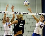 Kansas University's Andi Rozum, left, and Savannah Noyes, right, try to block Kansas State's Sandy Werner. The Wildcats won, 3-0, Wednesday night at Horejsi Center.