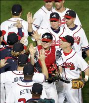Atlanta catcher Brian McCann, center, celebrates with teammates. The Braves defeated the Houston Astros, 7-1, Thursday night in Atlanta to even their National League series at one game apiece.